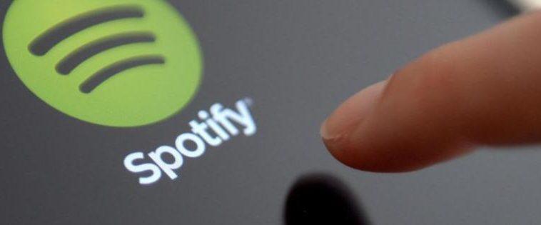 Dito che preme l'icona di Spotify